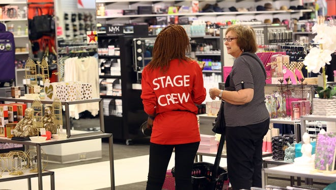 A sales associate assists a customer as shoppers get a sneak peek of the Macy's Backstage outlet store within the Macy's in Paramus, N.J., on Thursday.