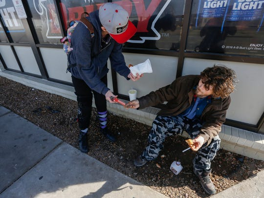 Mirenda Barrows gives a cigarette and an egg roll to a man who didn't give his name at the Route 66 Food Shop on Thursday, Feb. 15, 2018. Barrows was pregnant when she was hit by a truck while crossing the street in June 2017. She suffered extensive injuries and lost her baby.