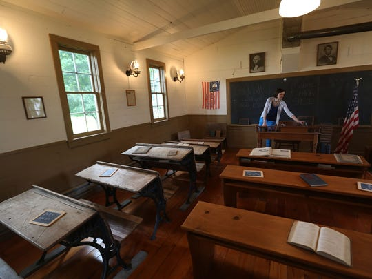 Kate Feil, director of the Story City Historical Society, stands in the Sheldall Schoolhouse, which opened in 1860 in Hamilton County and had been moved several times before becoming a museum in Story City. One of fewer than 3,000 remaining schoolhouses in Iowa (there were about 12,000 in 1901), the building received a new roof last year with help from a state grant program aimed at preserving old country schools.