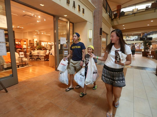 Marcus Do, 14, Jason Latta, 9, and his cousin Megan Latta, 13, haul bags filled with merchandise from a shopping expedition at Jordan Creek Town Center in West Des Moines in this file photo.