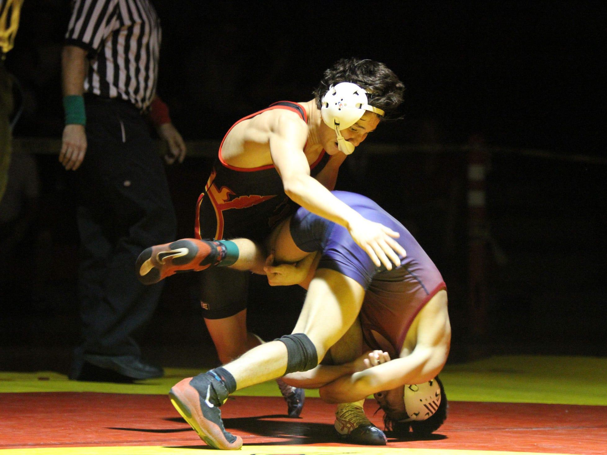 Palm Desert's Eric Santana, left, wrestles La Quinta's Joel Avila during the 113-pound match at Palm Desert High School on Thursday. Santana won after four overtime periods.