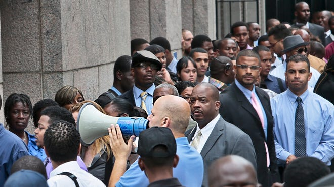 Job applicants listen to a speaker's bull horn instructions for attending a combined Metropolitan Transportation Authority (MTA) and Harlem Week job and career fair in New York in August 2013.