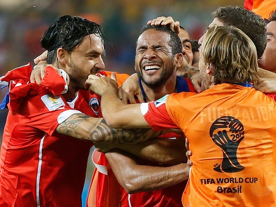 Chile's Jean Beausejour, center, celebrates with teammates after scoring his side's third goal during the group B World Cup soccer match between Chile and Australia in the Arena Pantanal in Cuiaba, Brazil, Friday, June 13, 2014.   (AP Photo/Frank Augstein)