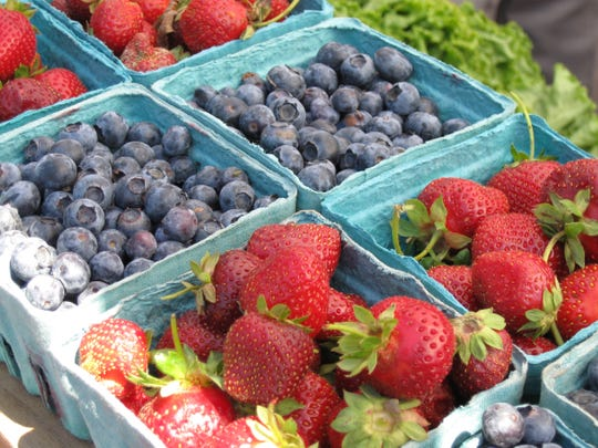 Early summer features a brief overlap between the end of strawberry season and the start of blueberry season, as shown here at last year's Downtown Tailgate Market in Asheville.