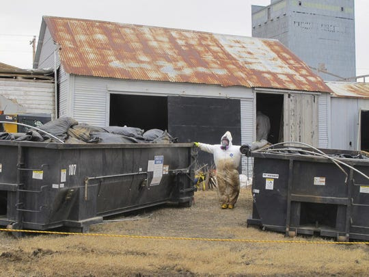 In this file photo taken April 23, 2014, white-suited workers wearing respirators clean up the illegal filter sock dump in an abandoned gas station in Noonan, N.D., near the Canadian border. Federal officials say fugitive James Ward, who escaped custody in Wyoming four years ago, is being sought for the illegal dumping of radioactive oilfield waste in North Dakota.