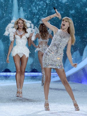 Taylor Swift performs as models walk the runway at the Victoria's Secret 2013 Fashion Show at the 69th Regiment Armory in New York City.