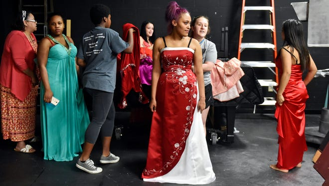 With help from York College sophomore Raelyn Saunders, William Penn junior Tatyana Aponte, center, tries on a donated prom dress alongside fellow students Thursday in William Penn's auditorium. York Suburban sophomore Elise Atkinson collaborated with William Penn principal secretary Yenitza Lindsay to collect about prom dresses from community members and stores to give to William Penn and West York students. Their efforts yielded about 700 donated dresses - too many to fit on the racks for the first giveaway - resulting in additional giveaways at future dates.