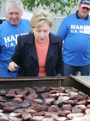 Sen. Hillary Clinton D-N.Y., takes a closer look at the steaks sitting on the grill at Tom Harkin's steak fry in Indianola Sept. 16, 2007.