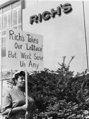 A protestor demonstrates against Rich's department