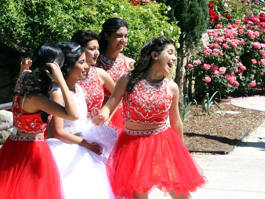 Martha Montano, right, laughs while posing for photos with quinceañera Brenda Cuellar, left, and other members of her court during a photo shoot at the Municipal Rose Garden on Saturday in Central El Paso. Now in its peak bloom, the garden's rose bushes display a variety of colors. According to the city's website, master gardeners planted 74 new rose bushes this year. The garden is open daily from 8 a.m. to 6 p.m. until Nov. 30. Visitors can enter for free. See more photos at elpasotimes.com.