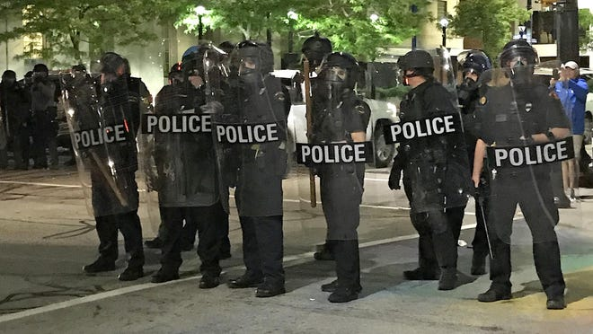 Erie police wearing riot gear line up on State Street at South Park Row in Erie on Saturday. Demonstrators hurled fireworks, glass bottles and frozen water bottles at police from Perry Square.