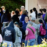 Parents wait to pick up students at North Thurston High School Monday, April 27, 2015, after a shooting at the school earlier in the morning. Police say no one was injured, and school district officials say the gunman has been apprehended by staff. (AP Photo/Ted S. Warren)