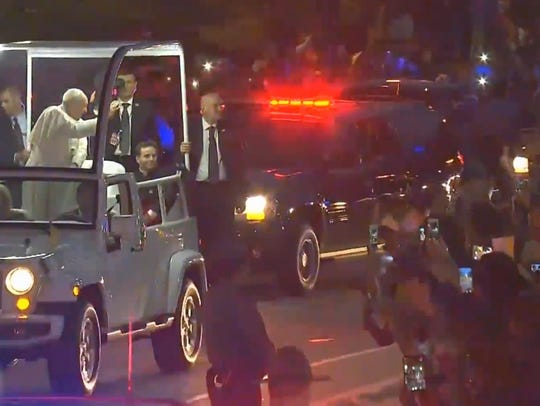 Pope Francis waves to crowds as he makes his way down
