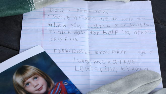 A photo of a 7-year-old Emily Ernspiker lay next to a letter she mailed along with a pair of gloves to workers cleaning up the 9/11 site.   She is now 23 and the letter's recipient Dave Triola was so touched he never used the gloves and keeps the note she attached tucked in them still.  July 26, 2017