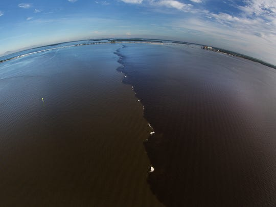 The demarcation line between the Gulf of Mexico and waters from the Caloosahatchee River can be seen near the Sanibel Causeway on September, 20, 2016.