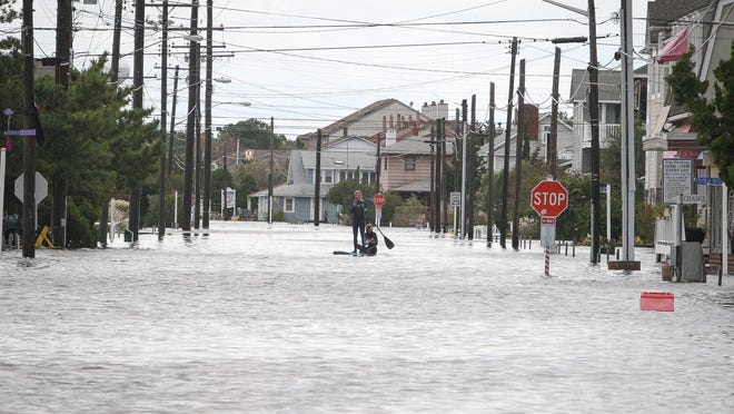 Zoe Jurusik of Ocean View and her friend Jenna Webb float along the flooded streets of Bethany Beach on a surf board on Oct. 30, 2012, a day after Superstorm Sandy moved through the area.