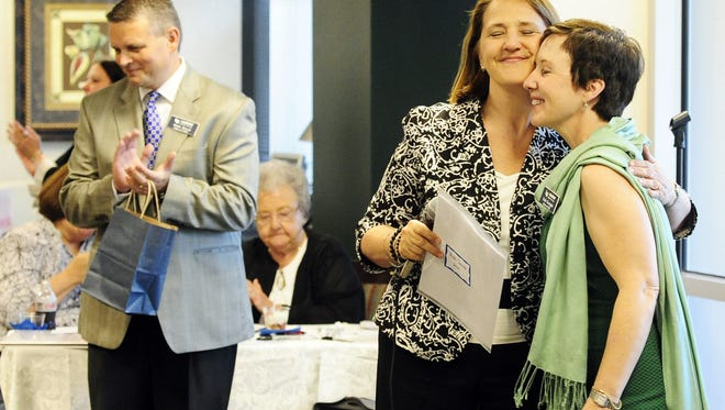 Co-chairwoman Vicki Smith, middle, hugs Dr. Deb Enright at a reception for the Leadership Brentwood Class of 2012.