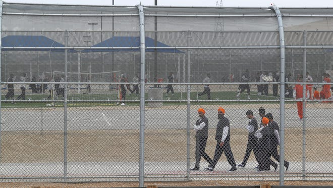 Detainees walk around outside at the U.S. Immigration and Customs Enforcement's Adelanto processing Center in Adelanto, Calif., on Dec. 3, 2019.