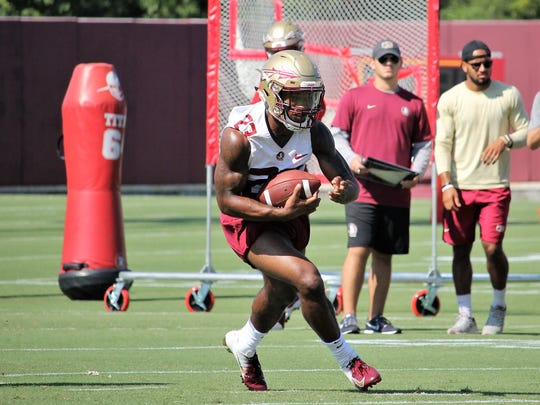 FSU RB Cam Akers takes a hand-off during the third practice of fall camp