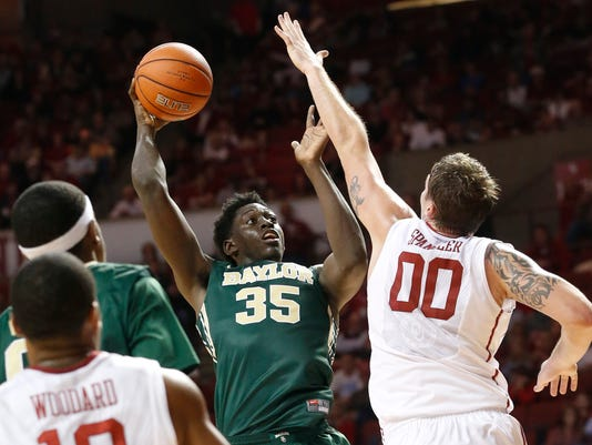 Baylor forward Johnathan Motley shoots as Oklahoma forward Ryan Spangler defends in the first half of an NCAA college basketball game in Norman, Okla., Saturday, Jan. 3, 2015. (AP Photo/Sue Ogrocki)