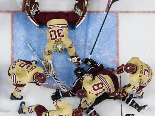 With the puck by Union's Daniel Carr's hand, Boston College's Thatcher Demko, center top, pokes it with his stick as Michael Sit (18), Ian McCoshen (3), Brendan Silk (9) and Michael Matheson (5) come to Demko's aid.