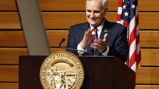 Gov. Mark Dayton applauds one of his invited guests as he delivers his State of the State address Wednesday at the University of Minnesota in Minneapolis.
