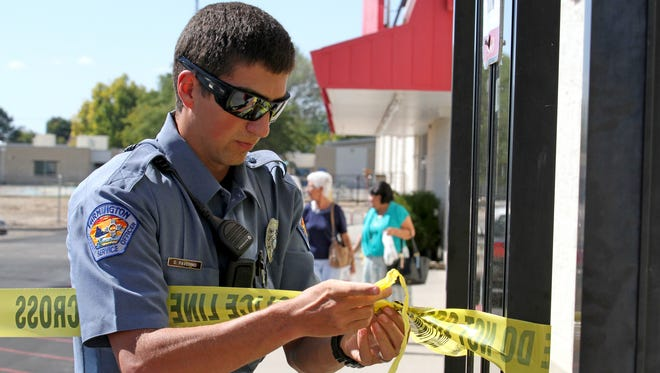Dylan Faverino, a community service officer with the Farmington Police Department, puts up crime scene tape after an accident on Thursday in the parking lot of Kmart on East Main Street in Farmington.