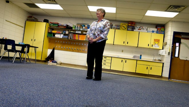 Bluffview Elementary School Principal Luanne Davis points out what she suspects is possible mold on her carpet Wednesday at her school in Farmington.