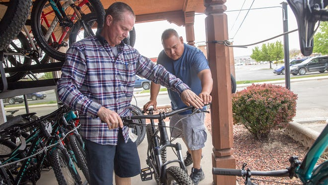 Mike Wulfert, left, helps costumer Matthew Yazzie select a bike on Monday at his store 505 Cycles in Farmington. The city of Farmington is pushing to diversify the local economy with similar outdoors-oriented businesses.