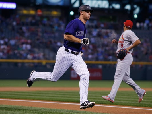 Colorado Rockies' DJ LeMahieu scores on a single hit by David Dahl as St. Louis Cardinals starting pitcher Carlos Martinez looks for the throw from the outfield in the first inning of a baseball game, Monday, Sept. 19, 2016 in Denver. (AP Photo/David Zalubowski)