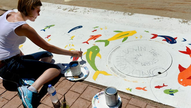 Kristi Wire, a graphic designer at Epicosity, paints a storm inlet in downtown Sioux Falls to bring clean water awareness as part of a painting project in partnership with the City of Sioux Falls, Sioux Falls Art Council and the Sioux Falls Green Business Program on Thursday, June 9, 2016.
