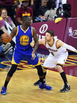 Golden State Warriors forward Draymond Green (23) handles the ball against Cleveland Cavaliers guard Matthew Dellavedova (8) during the second quarter in Game 4.