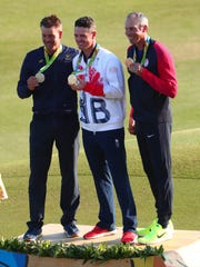 Sweden's Henrik Stenson, left, Great Britain's Justin Rose, center, and Matt Kuchar of the United States show off their medals.