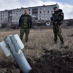 "Pro-Russian rebels look at an unexploded ""Uragan"" rocket in Debaltseve, eastern Ukraine on March 14."