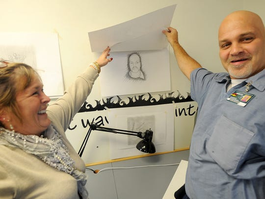 Lynnmarie Fye convinces inmate Justin Swiger to show off his self-portrait in her visual communications class at Richland Correctional Institution.