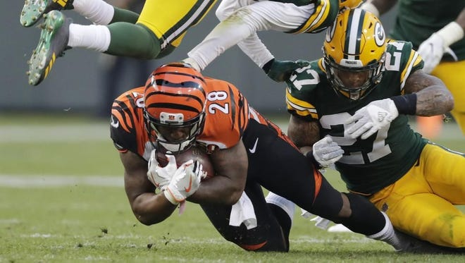 Cincinnati Bengals running back Joe Mixon (28) is tackled by Green Bay Packers safety Josh Jones (27) and cornerback Damarious Randall (23) in the fourth quarter on Sunday, September 24, 2017 at Lambeau Field in Green Bay, Wis.