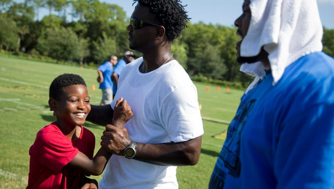 Immokalee High School graduate and former NFL all-pro Edgerrin James messes around with Jae James, 9, of Naples prior to the start of the 7th Annual Edgerrin James Football Skills Camp at North Park in Ave Maria, Fla. Monday, July 18, 2016.