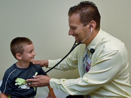Dr. Michael Colli uses Scott Eshleman, 6, to show how he would give a child an examination Thursday at a Keystone Health office. Scott does not have hand, foot and mouth disease, but it does strike children in his age group and younger most often, with symptoms that last about a week.
