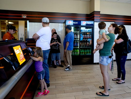 People stand in line Monday at Little Caesars on Lake
