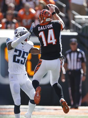 Cincinnati Bengals quarterback Andy Dalton (14) catches a touchdown pass in front of Tennessee Titans cornerback Blidi Wreh-Wilson (25).