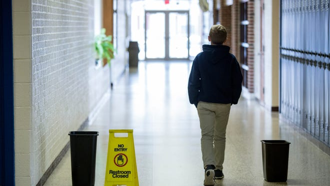 A student walks past trash cans collecting dripping water from a recent leak Thursday, Jan. 28, 2016 at Algonac Junior and Senior High School. Algonac Community Schools is considering a bond campaign to address facility and technology needs in the district, such a roof repairs.