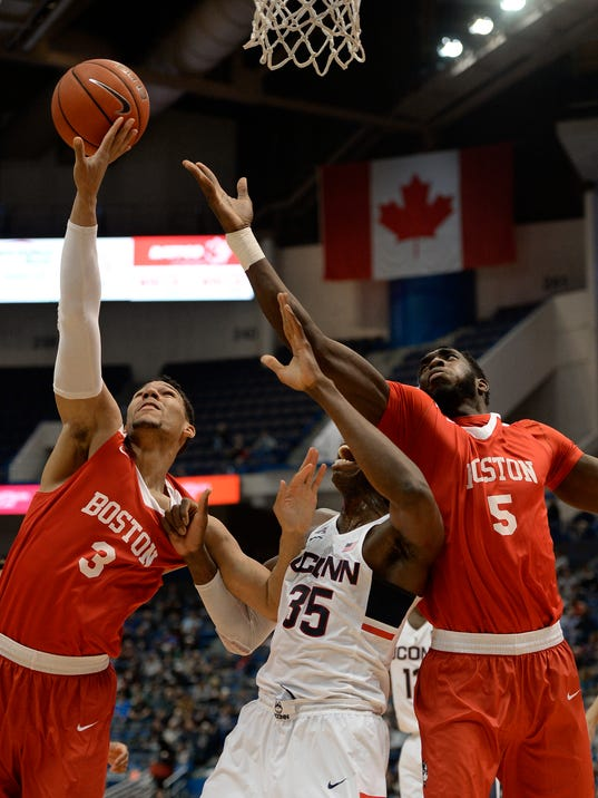 Boston University's Eric Fanning, left, grabs a rebound over Connecticut's Amida Brimah, center, as Boston University's Blaise Mbargorba, right, defends, in the first half of an NCAA college basketball game, Wednesday, Nov. 30, 2016, in Hartford, Conn. (AP Photo/Jessica Hill)