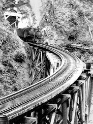 A historic railroad photo of a trestle and tunnel is