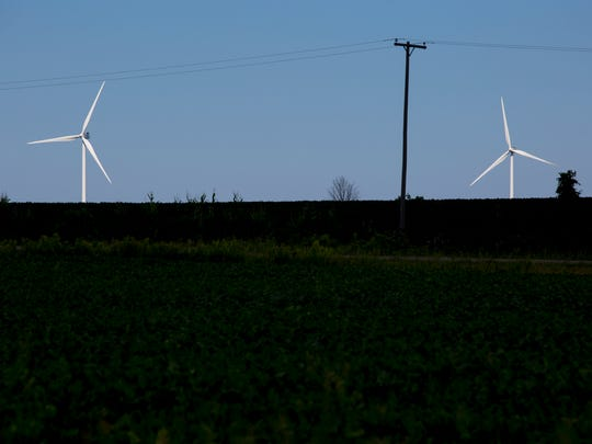 Wind turbines are seen beyond electrical lines Thursday, August 18, 2016 in Marion Township.