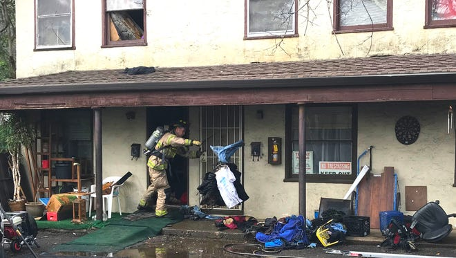 Firefighters clean out an apartment where a fire started Sunday when a resident tried to kill a spider using a torch lighter.