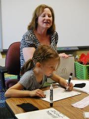 Kindergarten teacher Mary Axtell work with Lylah Pyszora