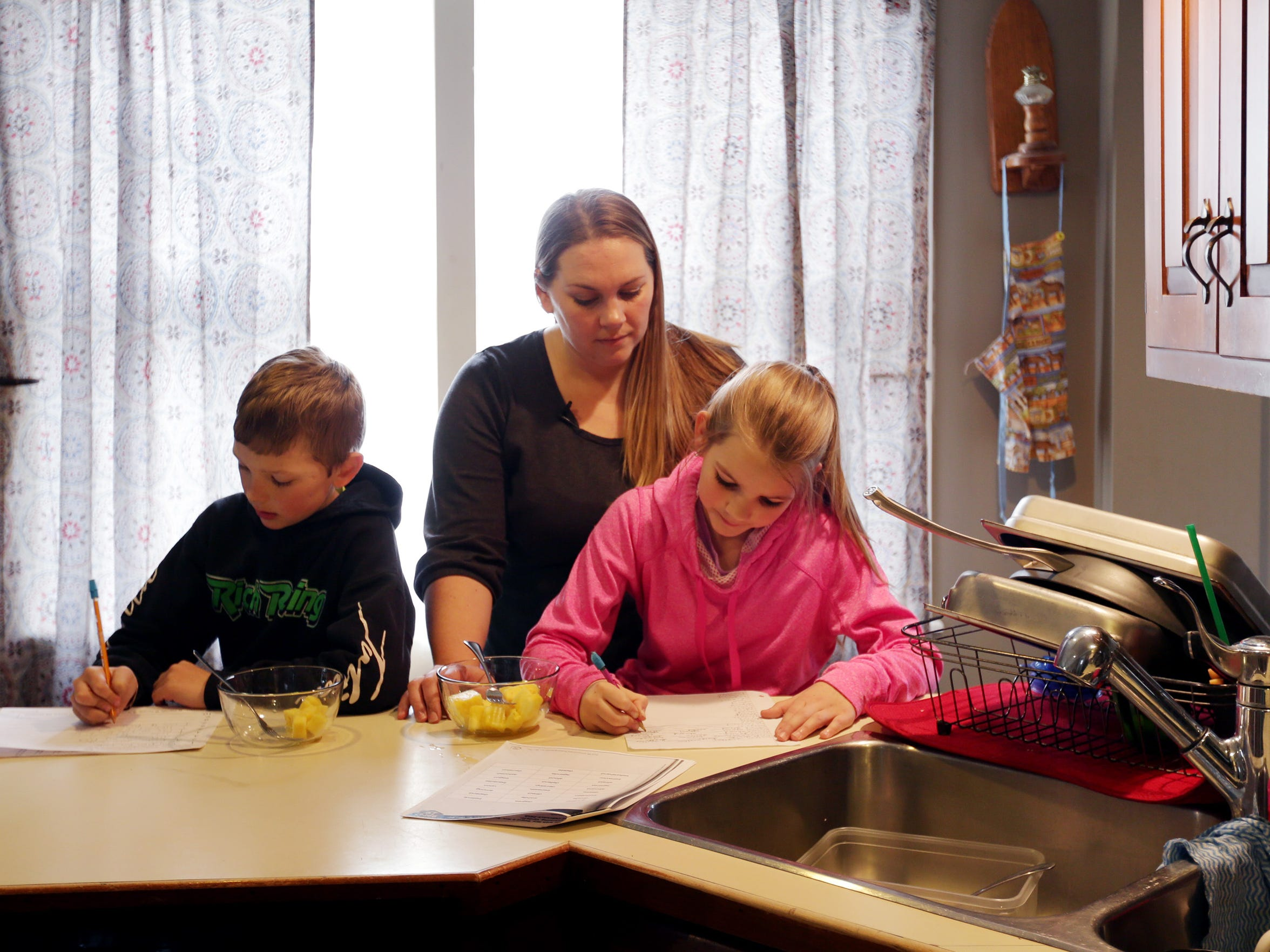 Nicole Rich, 34, helps her children Jamison Rich, 7, left and sister Jersey Rich, 9, with their homework at home March 3, 2016, in Ithaca, N.Y. Recent blood tests on Jamison showed lead results at twice the level for young children.