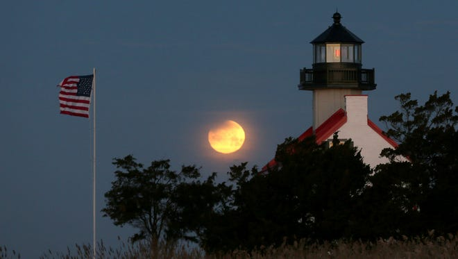 Earth's shadow begins to cross the upper left of the full moon Jan.  31, 2018, as it sets in the west behind the East Point Lighthouse in Cumberland County, N.J.
