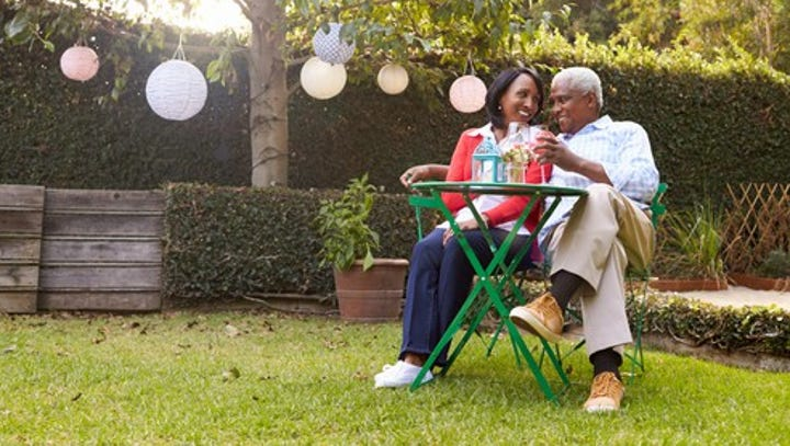 mature couple relaxing drinking wine together in their