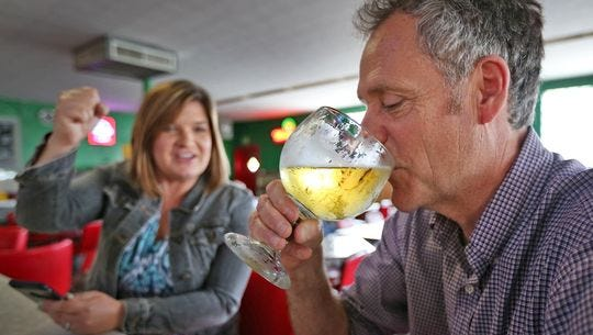 Indianapolis Star Beverage Reporter Amy Haneline (left) cheers on reporter Will Higgins as he drinks a 16-ounce Budweiser at The Workingman's Friend Restaurant and Bar.